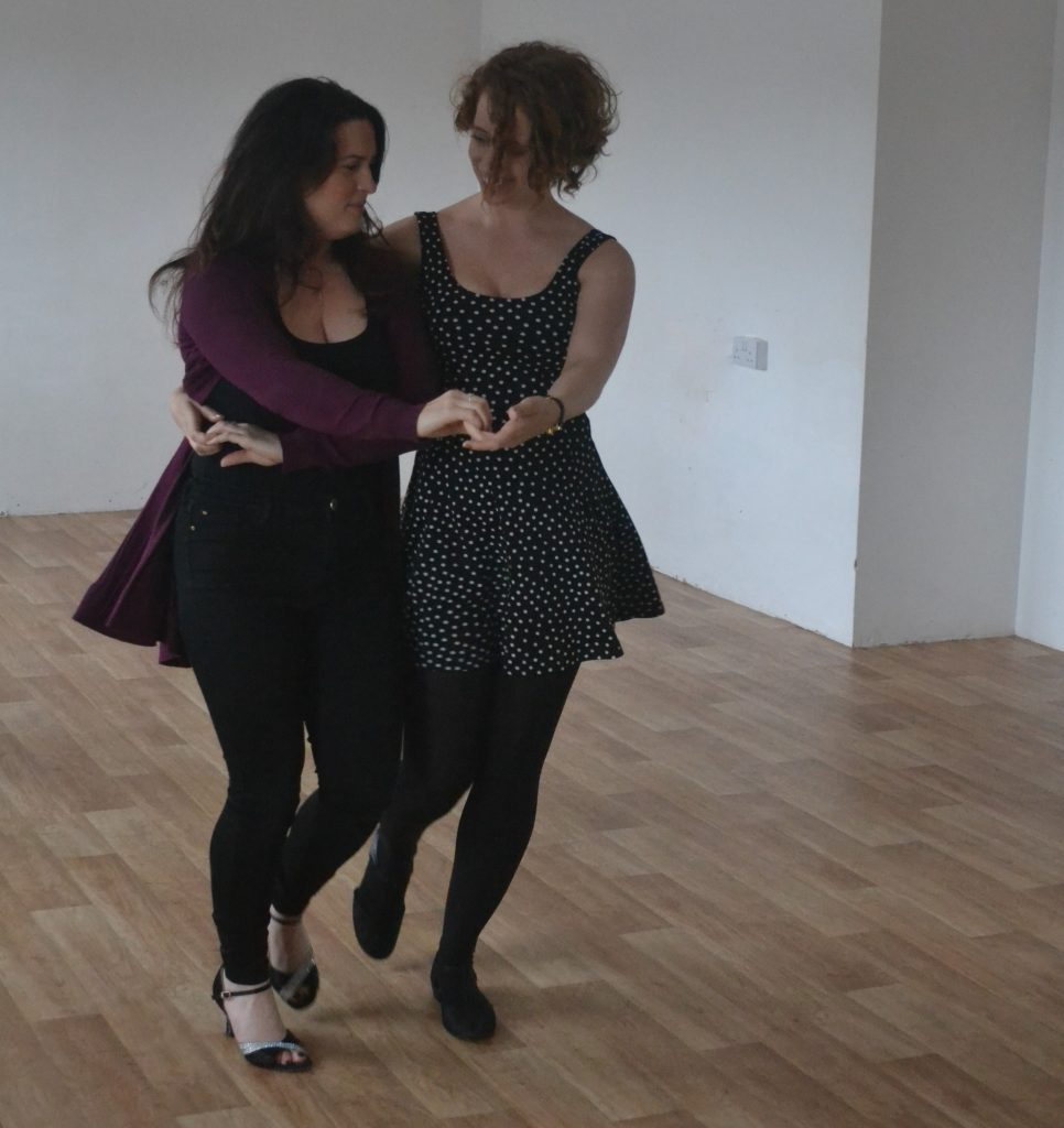 Two women dance bachata
