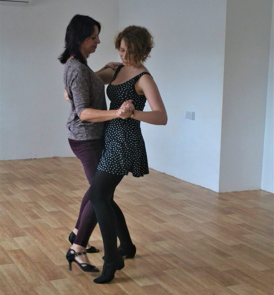 Two women dancing bachata